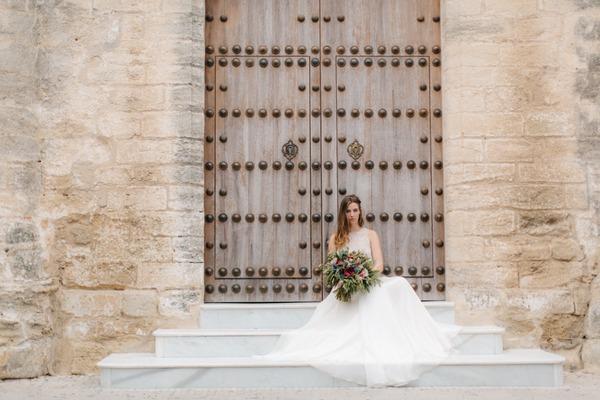 Bride sitting on steps in front of large door