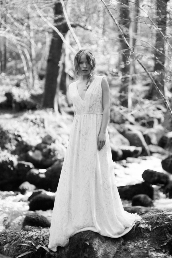 Bride standing by stream