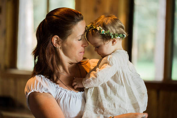 Lady holding baby flower girl with flower crown