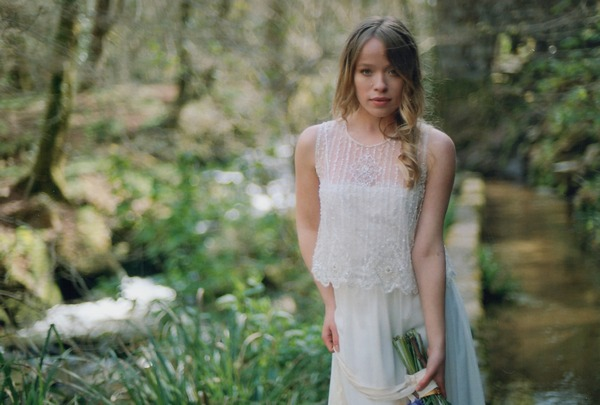 Bride in lace two-piece dress holding bouquet