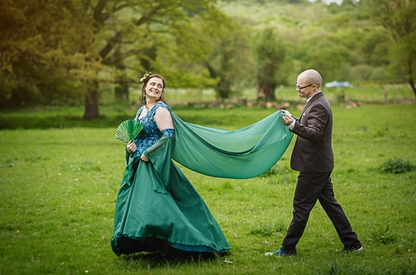 Groom holding train of bride's green dress
