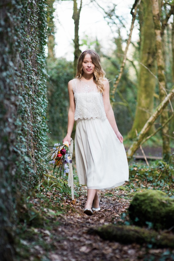 Bride holding out dress as she walks through woods