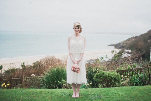Bride standing up straight holding bouquet
