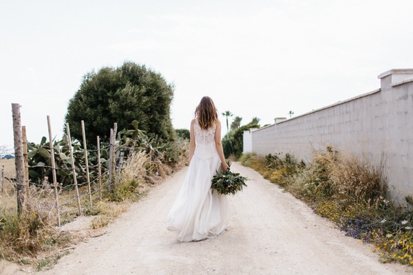 Bride carrying bouquet down street in Spain