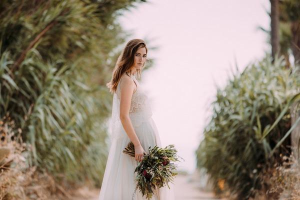 Boho bride holding rustic bouquet