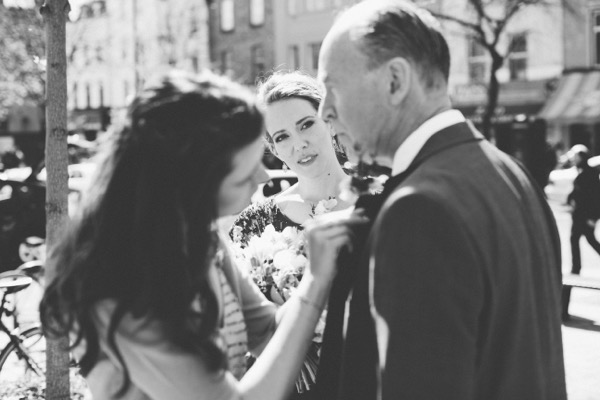 Bride watching as father has his buttonhole attached