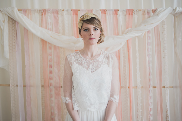 Bride standing in front of pink wedding ceremony backdrop