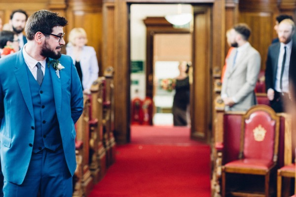 Groom turning to watch bride walk down the aisle