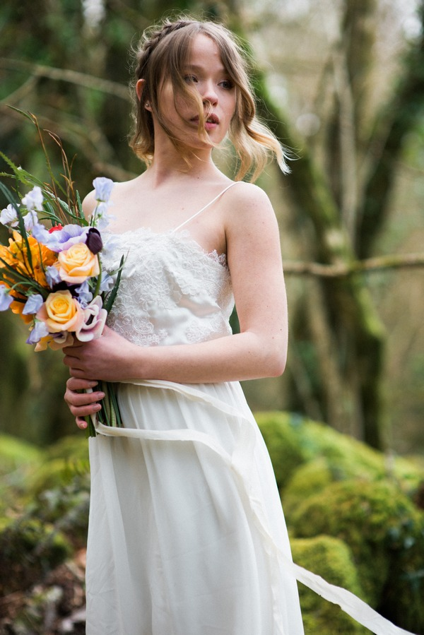 Bride in lace wedding dress holding bright bouquet