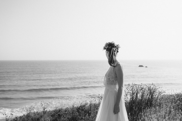 Boho bride with flower crown looking at sea
