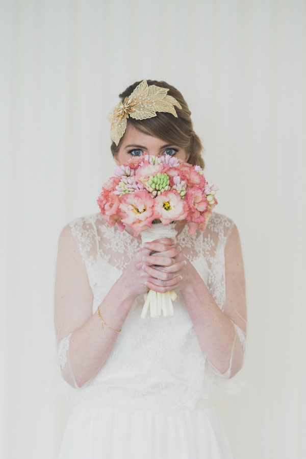 Bride holding pink bouquet in front of face