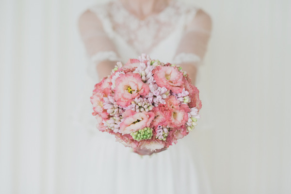 Bride holding out pink wedding bouquet