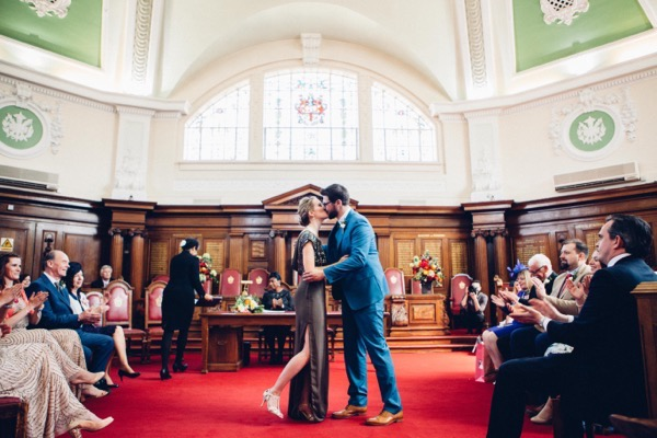Bride and groom kiss in Islington Town Hall