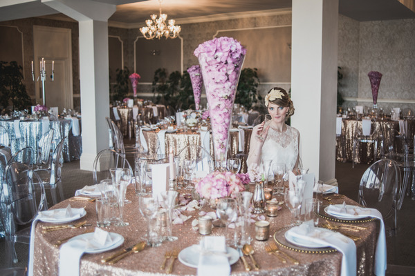 Bride sitting at wedding table with pink and metallic gold styling