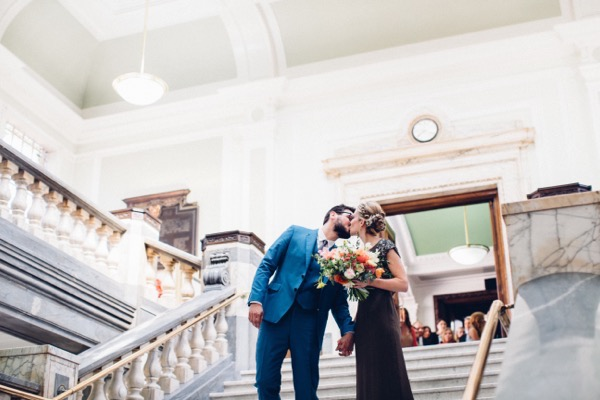 Bride and groom kissing on steps of Islington Town Hall