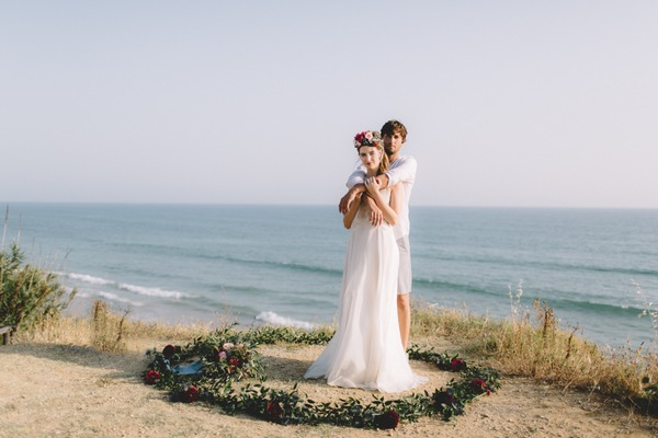 Bride and groom standing in circle of flowers on beach