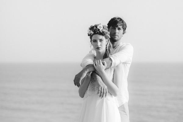Groom with arms around boho bride