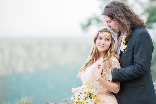 Groom standing behind bride kissing her head