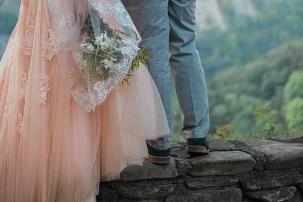 Legs of bride and groom standing on wall
