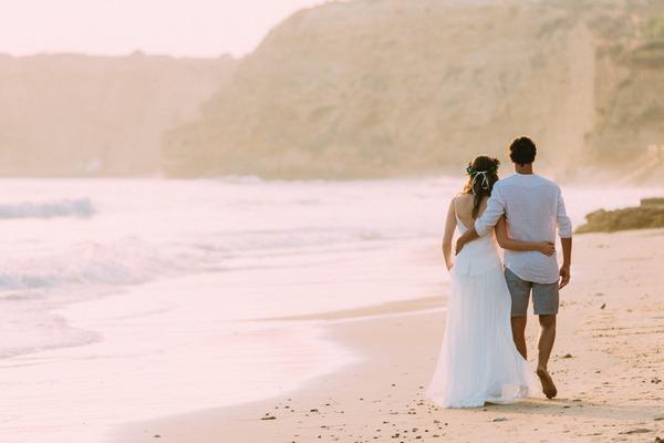 Bride and groom walking on beach in Spain
