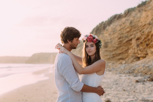 Boho bride wearing flower crown with arms around groom
