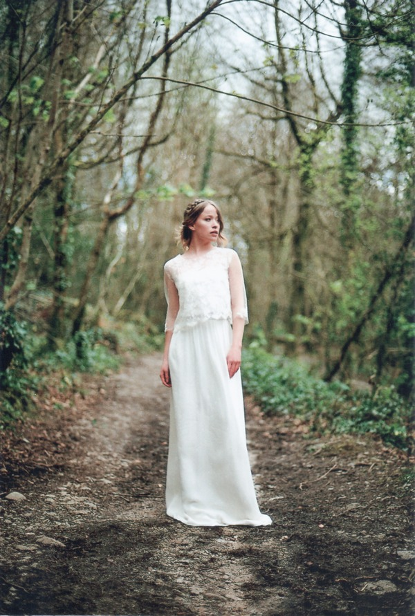 Bride standing in clearing in woodland