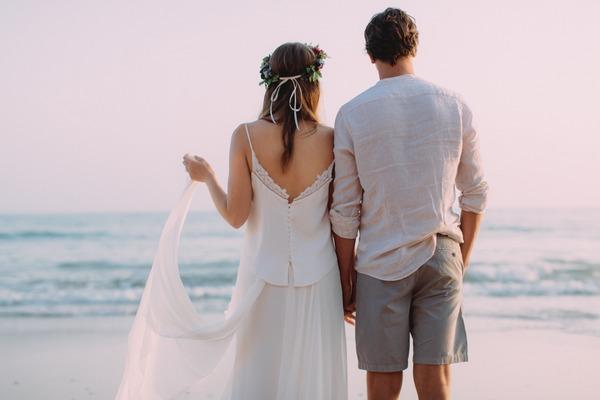 Boho bride and groom looking at sea