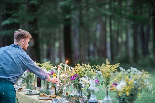 Man lighting candles on long wedding table