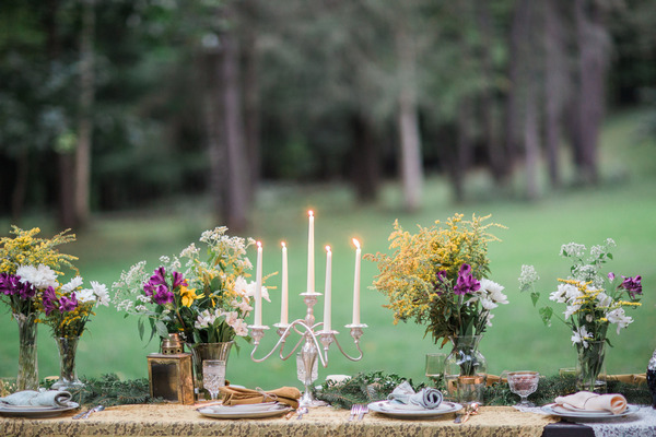 Candlestick and rustic flowers on long wedding table