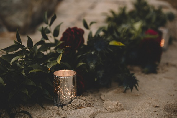 Tea light and wedding flowers on beach