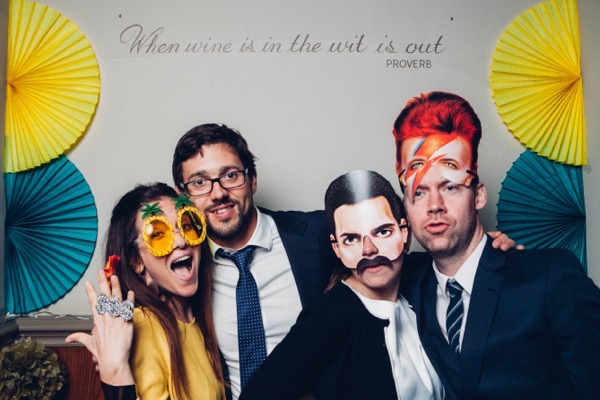 Wedding guests posing with props in wedding photo booth