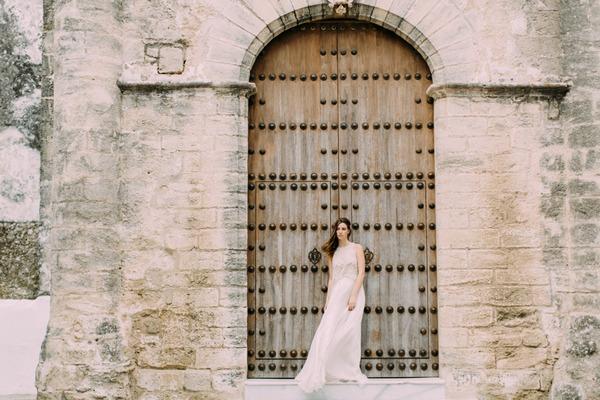 Bride standing up against large door