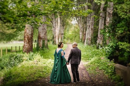Bride and groom holding hands on path in woodland