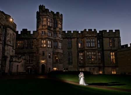Bride and groom outside Warwick Castle at night