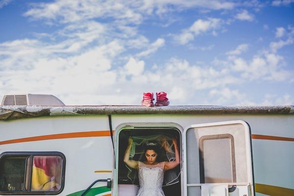 Bride putting on veil as she leaves caravan
