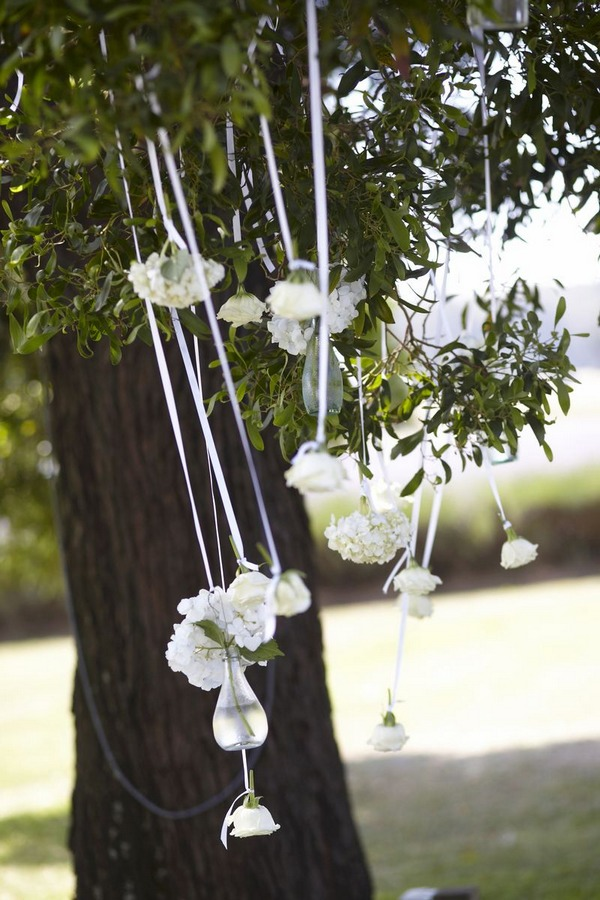 Vases of flowers hanging from tree