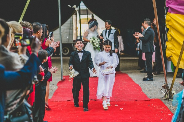 Pageboy and flower girl walking down aisle for circus wedding