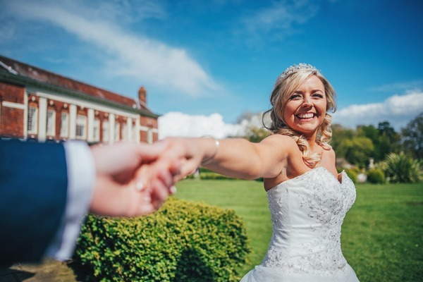 Bride smiling as she holds groom's hand - Picture by Three Flowers Photography