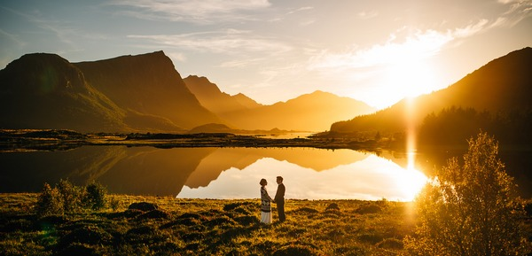 Bride and groom standing in front of incredible landscape as sun sets - Picture by Nordica Photography