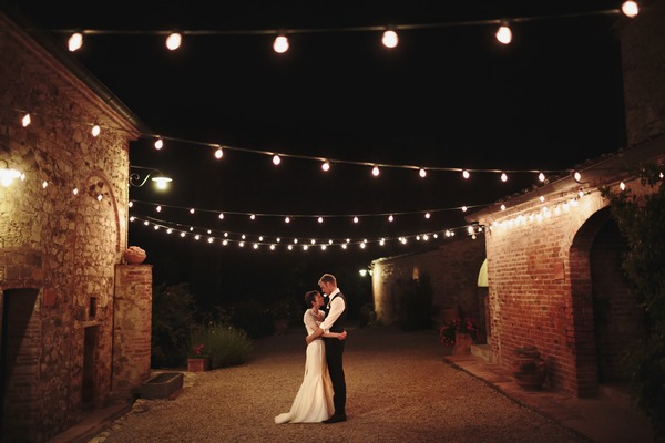 Bride and groom standing in courtyard at night with strings of light bulbs overhead - Picture by Paul Fuller Photography