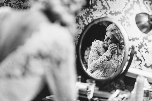 Reflection of bride in mirror putting earring on - Picture by Andy Turner Photography