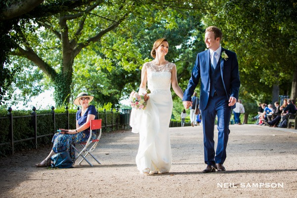 Woman smiling at bride and groom walking holding hands - Picture by Neil Sampson Photography