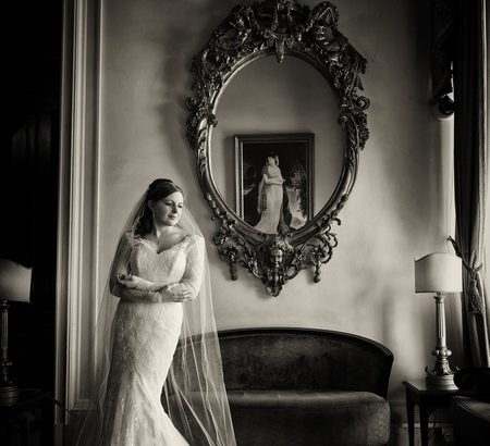 Bride standing by mirror - Picture by Pauls Studio