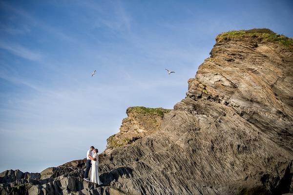 Bride and groom standing on cliff with seagulls flying overhead - Picture by Katherine Ashdown Photography