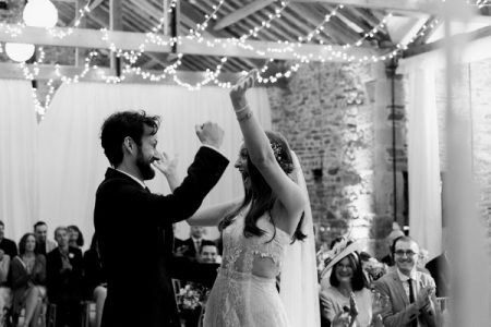Happy bride and groom with arms in the air after getting married - Picture by Folega Photography