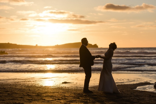 Bride and groom holding hands on beach at sunset - Picture by Stewart Girvan Photography