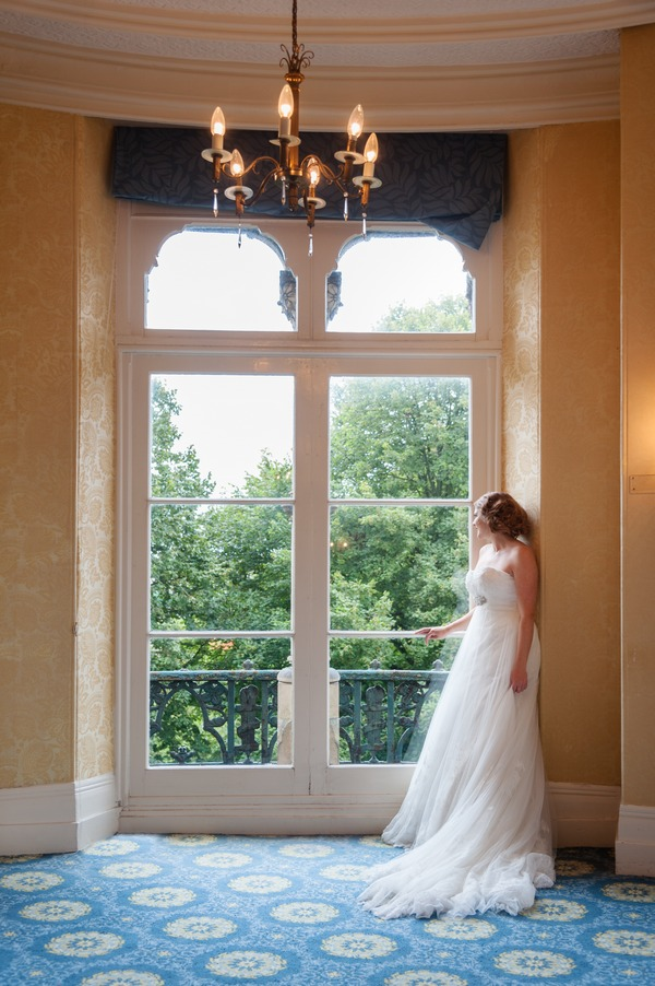 Bride looking out of the window of The Duke of Cornwall Hotel