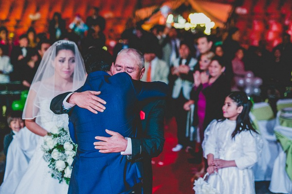 Bride's father hugging groom