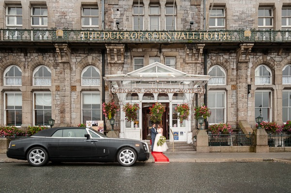 Bride and groom outside entrance of The Duke of Cornwall Hotel
