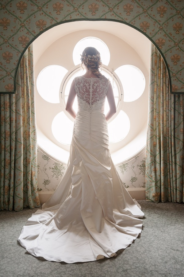 Bride looking out of flower window at The Duke of Cornwall Hotel